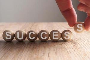Hand setzt Erfolgswort in Holzkugel geschrieben foto