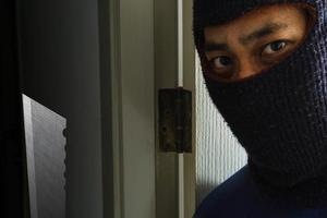 maskierter Räuber mit Messer versteckt sich hinter der Tür foto