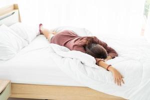 schöne asiatische frau, die morgens im bett schläft foto