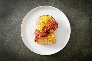 Brottoast mit Rührei und Speck auf weißem Teller foto