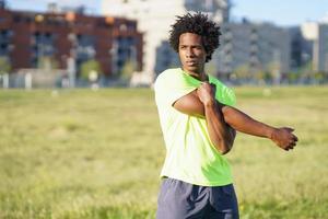 schwarzer Mann mit Afro-Haar, der sich nach dem Laufen im Freien dehnt. foto