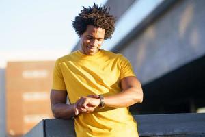 schwarzer Mann, der seine Smartwatch konsultiert, um seine Trainingsdaten anzuzeigen. foto