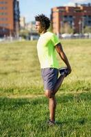 schwarzer Mann, der seinen Quadrizeps streckt, nachdem er im Freien gelaufen ist. foto