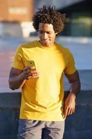 schwarzer Mann konsultiert sein Smartphone, während er sich von seinem Training ausruht. foto