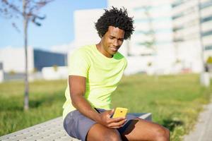 schwarzer Mann konsultiert sein Smartphone foto