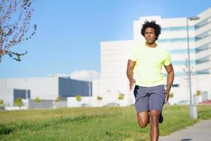 schwarzer athletischer Mann, der in einem Stadtpark läuft. foto
