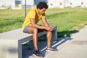 schwarzer Mann konsultiert sein Smartphone mit einer Übungs-App foto
