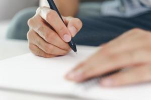 Nahaufnahme von Mannhänden auf dem Notizblock notieren, Notebook mit Stift foto