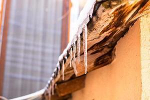 Dach mit Schnee bedeckt, Eiszapfen auf dem Dach isoliert aus nächster Nähe. foto