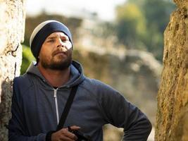 bärtiger Mann in Jacke mit Kapuze posiert in einer Schlucht einer Festung foto