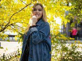 süßes blondes Mädchen mit wallendem Haar in einer Jeansjacke foto