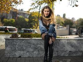 attraktives Mädchen mit schönen wallenden Haaren sitzt auf einer Bank foto