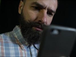 stylischer Mann mit Bart und Schnurrbart schaut auf ein Handy foto