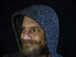 Porträt eines Mannes mit Bart in der Kapuze mit einem lächelnden Gesicht foto