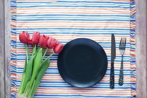 Besteck und leerer Teller auf Holzuntergrund von oben nach unten foto