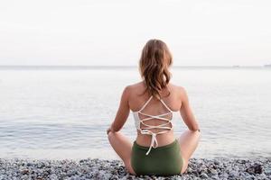 Rückansicht einer jungen Frau, die am Strand meditiert foto