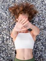 junge lächelnde Frau liegt am Steinstrand und bedeckt das Gesicht mit den Händen foto