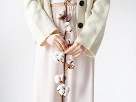 schöne Frau in gemütlicher Kleidung, die einen Zweig von Baumwollblumen hält foto