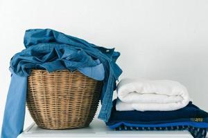 Kleidung im Korb hautnah und Stoff auf der Waschmaschine stapeln foto