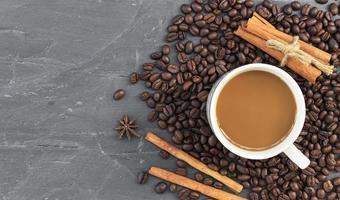 Tasse Kaffee und Kaffeebohnen auf Steinhintergrund foto