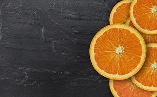 oranger frischer Schnitt auf schwarzem Stein foto