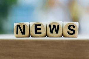 Nachrichtenkonzept mit Holzklotz auf Holztischhintergrund foto