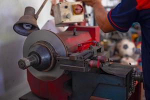 Mechaniker, der die Bremse repariert, verwendet Drehbankwerkzeug, das Scheibenbremsen poliert foto