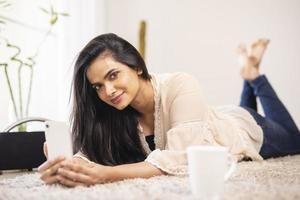 Attraktive junge indische Frau, die sich zu Hause mit dem Handy entspannt. foto