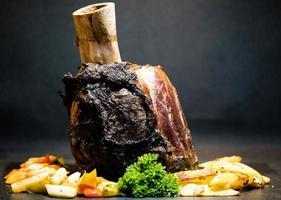 Rinderhammer - ein Schmorbraten vom Unterschenkel einer Kuh mit Gemüse foto
