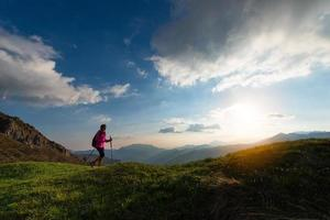 Schlanke Frau, die Nordic Walking in den Bergen praktiziert foto