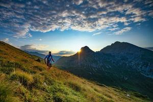 Skyrunner Läufer läuft in den Bergen, wenn die Sonne aufgeht foto