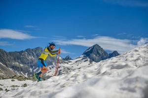 Skyrunning-Training mit Stöcken im Schnee bergauf foto