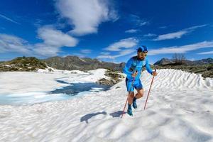 Skyrunner Mann bergauf in einer verschneiten Strecke foto