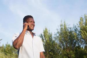 glücklicher Afroamerikaner mit einem Telefon auf der Straße foto