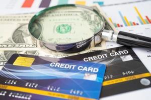 Kreditkartenmodell mit Lupe, finanzielle Entwicklung foto
