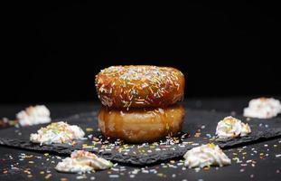 Donuts mit Erdbeersirup und farbigem Topping mit Sahne foto