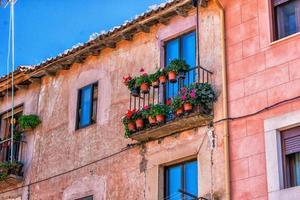Fassade mit Balkon und Pflanzen im Sommer foto