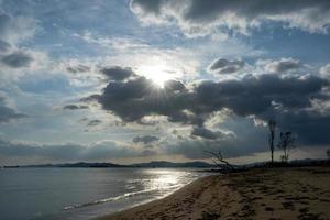 Seelandschaft mit Silhouetten von Bäumen und Schiffen im Hintergrundlicht. foto