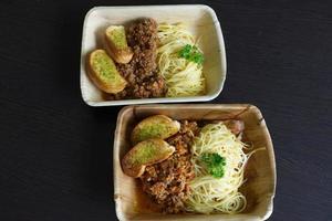 Spaghetti-Schweinefleisch-Tomatensauce mit einer Scheibe Knoblauchbaguette foto