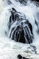 fließender Wasserfall in verschwommener Bewegung über schwarzem Felsen. foto