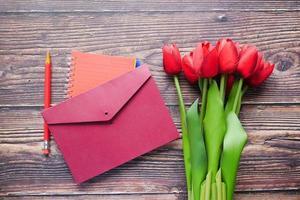 Umschlag und rote Tulpe auf dem Tisch foto