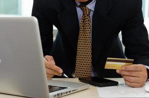 Geschäftsmann, der eine Kreditkarte hält, um Online-Marketing einzukaufen foto