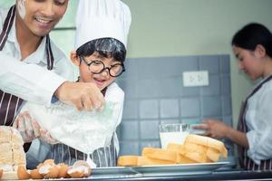 asiatischer Mann, Frau und Junge mit Brille kochen foto