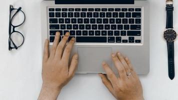 Draufsicht Hand von Laptop, Brille und Uhr auf weißem Hintergrund on foto