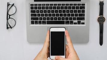 Smartphone über Laptop, Tablet-Stift, Brille und Uhr auf Weiß foto