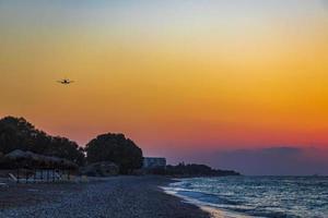 Flugzeug landet bei farbenfrohem Sonnenuntergang Ialysos Strand Rhodos Griechenland. foto