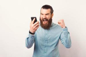 Foto von wütendem bärtigem Geschäftsmann, der auf Smartphone schreit