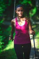 eine junge Frau übt Nordic Walking foto