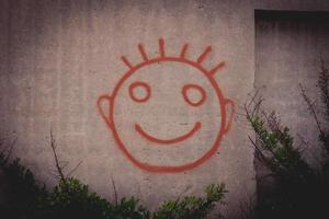 Graffiti-Gemälde von rotem glücklichem Smiley-Gesicht auf einer Betonwand foto