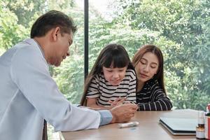 Gesundheitsberatung des asiatischen männlichen Arztes mit Mutter und Kind. foto